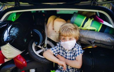 Niño pequeño con máscara facial sentado en la bota de coche cargado en el campo, concepto de viaje local .
