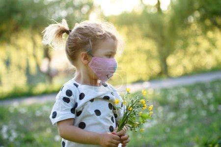 Photo pour Petite fille avec masque facial debout à l'extérieur et cueillette de fleurs, concept de coronavirus . - image libre de droit