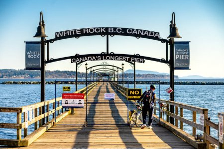 Photo for White Rock, Canada - March 25, 2020: Pier closed to general public during time of Covid-19 pandemic. Notification signs are affixed to fence blocking access to the popular pier. - Royalty Free Image