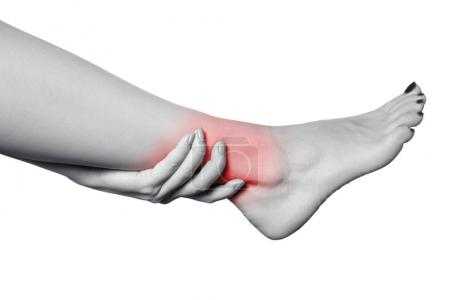 Closeup view of a young woman with pain on leg. isolated on white background. Black and white photo with red dot.