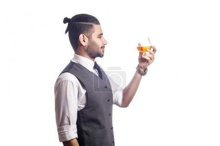 Handsome bearded businessman holding a glass of whiskey.