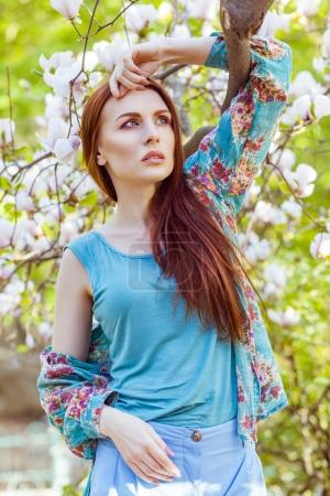 Portrait of young beautiful woman posing among blooming trees with pink eyeshadow.