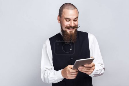 Photo for Handsome businessman with beard and handlebar mustache holding digital tablet looking at screen with toothy smile. studio shot, on gray background. - Royalty Free Image