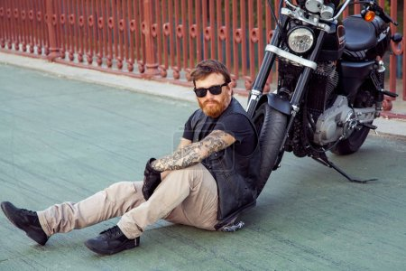 redhead biker with beard in leather jacket and bike.