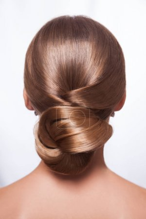 Back view of beautiful woman with creative elegant hairstyle