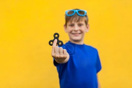 Boy with fidget spinner on yellow background.