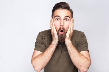 Portrait of surprised bearded man with dark green t shirt against light gray background. studio shot.