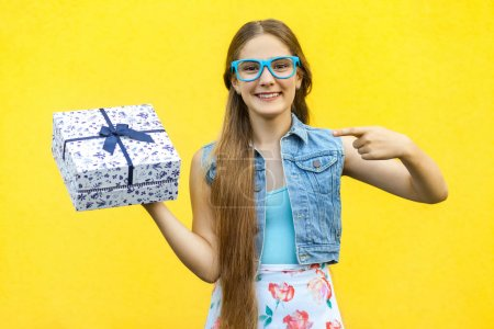 The beautiful smiling girl in dress and blue glasses, pointing finger on present box and toothy smile, isolated over yellow background. Indoor studio shoot
