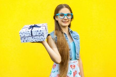 Portrait of a happy hipster smiling girl in dress and blue glasses, holding present box and toothy smile isolated over yellow background. Indoor studio shoot