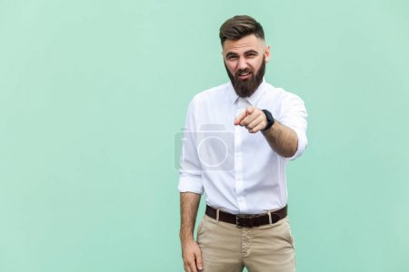 Photo for The bearded man pointing finger at camera and mockery over someone. Indoor, studio shot - Royalty Free Image