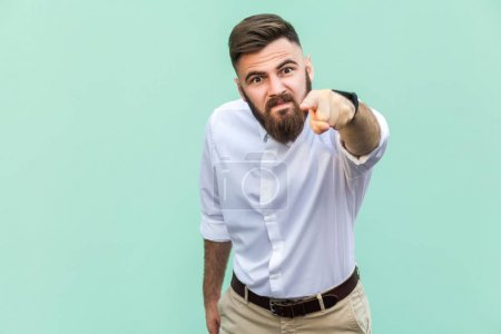Angry bearded businessman with white shirt looking at camera and pointing finger to you. Studio shot isolated on light green background.
