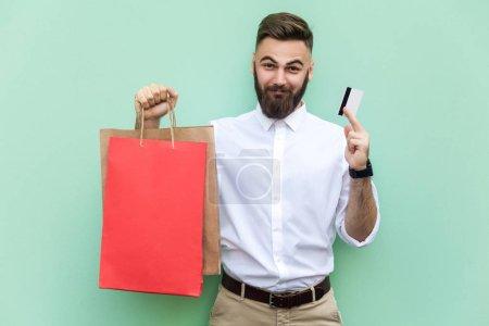 Photo pour Jeune homme d'affaires adulte utilisant une carte de crédit pour faire des achats ou des opérations bancaires en ligne. Tenir la carte de crédit sur les mains et regarder la caméra et sourire. Intérieur, prise de vue studio. Fond vert clair - image libre de droit