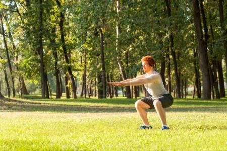 Sit ups. Young adult redhead man having intensive training outdoors in morning