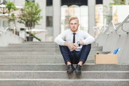 Photo for Unfair ginger worker sit on stair and seriosly looking at camera. Outdoor - Royalty Free Image