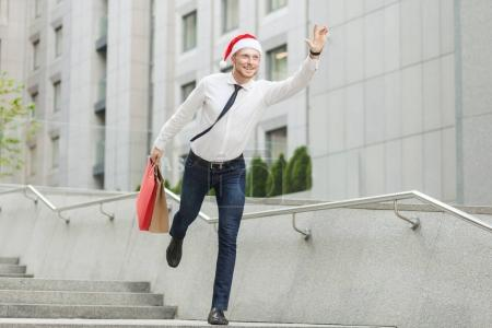 Young adult bearded man in santa hat holding many shopping bags and gifts and running to kids.