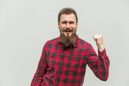 Photo for Celebrating success. Young adult businessman keeping arm raised and expressing positivity while standing indoors with gray background. Studio shot - Royalty Free Image