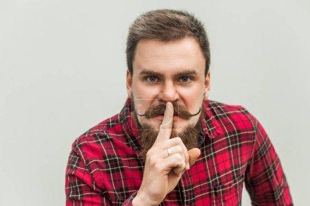 Photo pour Signe. Homme d'affaires en colère avec barbe et moustache du guidon regardant la caméra avec signe silencieux. plan studio, sur fond gris . - image libre de droit