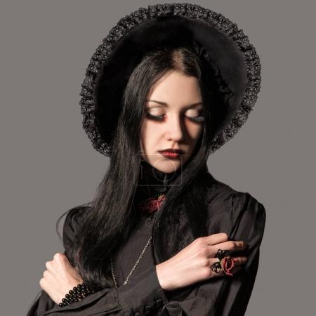 Portrait of brunette woman in black dress and classic gothic sty