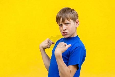 Photo pour Oui ! Le bonheur beau garçon en t-shirt bleu, en regardant la caméra, célèbre la victoire. Studio isolé tourné sur fond jaune - image libre de droit