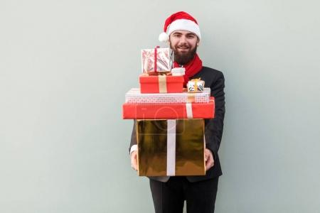 Businessman holding many gift box and looking at camera and toot