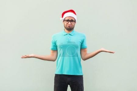 Photo pour Perplexe le Barbu en chapeau de Noël avec les bras, haussant les épaules, en disant: qui se soucie, alors quoi, je ne sais pas. Studio isolé tourné sur fond gris. - image libre de droit
