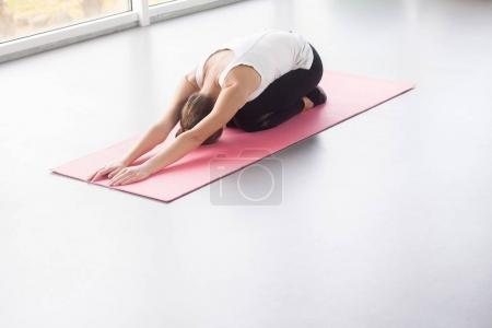 young woman doing yoga while lying in child posture in gym