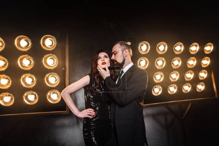 bearded businessman touching chin of sensual ginger woman in night club