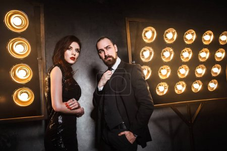 well dressed couple posing near stage with lamps, luxury and richly concept