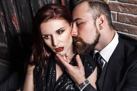 handsome bearded man kissing redhead sensual woman, love and passion concept, closeup