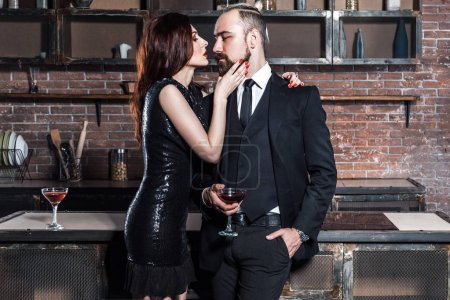 redhead sensual woman kissing well dressed bearded man in loft interior