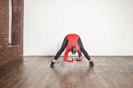sporty blonde woman practicing yoga while standing in uttanasana pose on wooden floor
