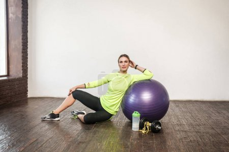 sporty woman leaned on violet fitness ball and relaxing while sitting on wooden floor, weight loss concept