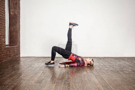 woman in sportswear practicing in stretching while lying on wooden floor