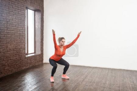 woman in sportswear squatting with hands up in front of window