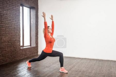 adult woman in sportswear  practicing in stretching and squatting with hands up in front of window