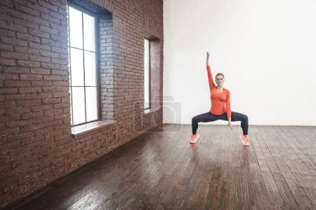 activity woman looking at camera and doing balance squat pose