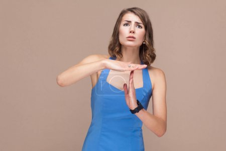 woman in blue dress showing pause gesture, need time out concept