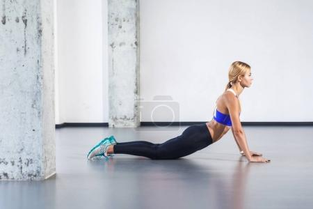 blonde activity woman practicing yoga posture of cobra