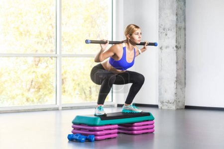 Blonde woman doing squats on step platform with barbell bar