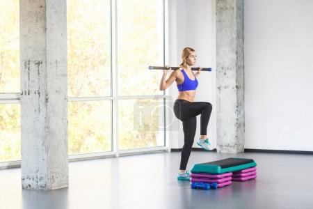 sporty woman holding barbell bar and practicing on step platform