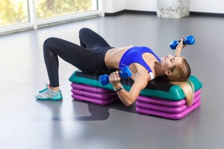 blonde woman lying on step platform and doing exercise with dumbbells in gym