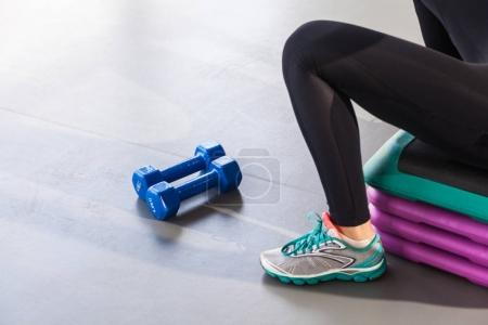 female legs in sneakers near step platform and dumbbells in gym, close-up
