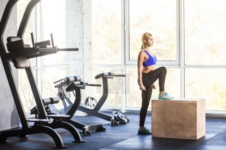 woman in gym doing cross fit exercise step up on cube
