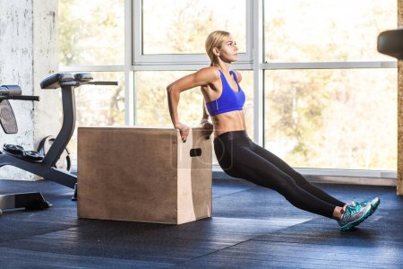 Woman doing reverse push-up on triceps and biceps on crossfit cube in gym