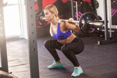 athlete woman sitting with barbell in gym