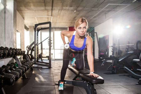 blonde sporty bent woman push-ups dumbbell in gym