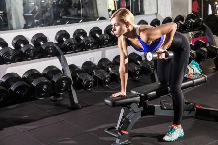 bent woman training bicep with dumbbell in gym
