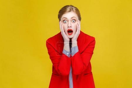 Photo pour Femme d'affaires rousse choquée en veste rouge avec bouche ouverte regardant la caméra, bon nouveau concept - image libre de droit