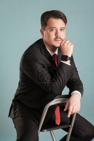 portrait of pensive businessman sitting on chair and looking at camera on light blue background