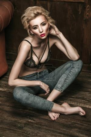 tempting blonde model in black lace bra and jeans sitting on wooden floor near leather sofa